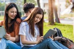 Étudiants heureux d'amis de groupe s'asseyant en parc à l'université Photographie stock