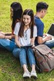 Étudiants heureux d'amis de groupe s'asseyant en parc à l'université Photographie stock libre de droits