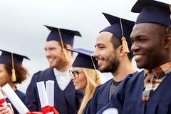 Étudiants heureux dans des panneaux de mortier avec des diplômes Photo stock