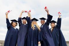 Étudiants heureux dans des panneaux de mortier avec des diplômes Photographie stock libre de droits