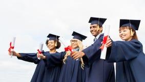 Étudiants heureux dans des panneaux de mortier avec des diplômes Images libres de droits