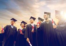 Étudiants heureux dans des panneaux de mortier avec des diplômes Photographie stock
