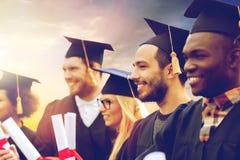 Étudiants heureux dans des panneaux de mortier avec des diplômes Photos stock