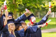 Étudiants heureux dans des panneaux de mortier avec des diplômes Images stock