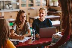 Étudiants heureux discutant des études dans la salle de classe Image libre de droits