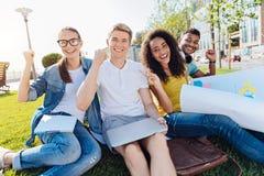 Étudiants heureux faisant des poings tout en posant sur l'appareil-photo Image stock