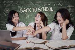 Étudiants heureux joignant des mains Images stock