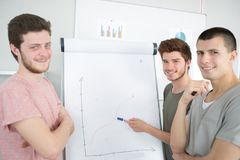 3 étudiants heureux montrant le diagramme dans la salle de classe Image stock
