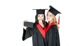 Étudiants heureux prenant le selfie sur le smartphone d'isolement sur le blanc Photo libre de droits
