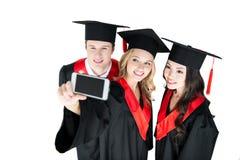 Étudiants heureux prenant le selfie sur le smartphone d'isolement sur le blanc Photos stock