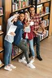 Étudiants heureux se tenant dans la bibliothèque tandis que faites le selfie Photographie stock