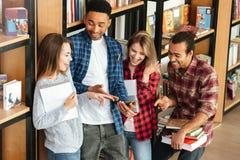 Étudiants heureux se tenant dans la bibliothèque utilisant le téléphone portable Images libres de droits