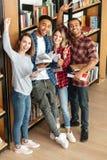 Étudiants heureux se tenant dans le livre de lecture de bibliothèque Image stock