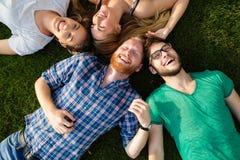 Étudiants heureux se trouvant sur la terre et le sourire Photographie stock libre de droits