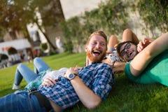 Étudiants heureux se trouvant sur la terre et le sourire Photographie stock