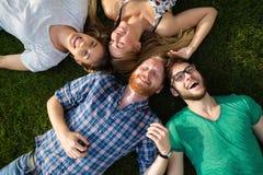 Étudiants heureux se trouvant sur la terre et le sourire Image libre de droits