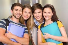 Étudiants heureux tenant des dossiers au couloir d'université Image stock