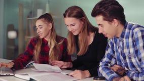 Étudiants heureux travaillant à leur travail se reposant ensemble à la table et au café potable Groupe des jeunes sur banque de vidéos