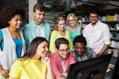 Étudiants internationaux avec des ordinateurs à la bibliothèque Photographie stock libre de droits