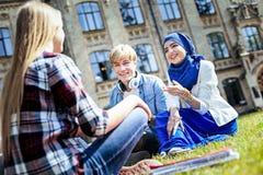Étudiants internationaux bavardant tout en détendant sur l'herbe dehors Image libre de droits