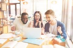 Étudiants internationaux comblés s'asseyant dans le café Photos stock