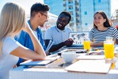 Étudiants internationaux occupés heureux discutant le projet d'université Photographie stock