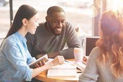 Étudiants internationaux positifs étudiant dans le café Photo stock