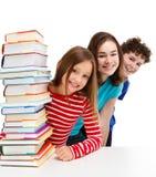Étudiants et pile des livres images stock