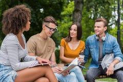 Étudiants joyeux causant dans le campus dehors Photo stock