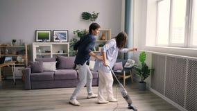 Étudiants joyeux nettoyant le plancher avec la danse d'aspirateur riant ensemble banque de vidéos