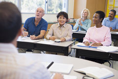 Étudiants mûrs et leur professeur dans une salle de classe images libres de droits