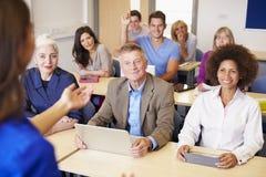 Étudiants mûrs dans la classe d'éducation plus permanente avec le professeur image libre de droits