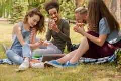 Étudiants mangeant de la pizza tout en étudiant sur l'herbe Photographie stock libre de droits