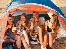 Étudiants mangeant des nouilles près de la tente sur un fond naturel Couples sur des vacances en camping Voyageant et augmentant  Images libres de droits