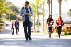 Étudiants marchant dehors sur le campus universitaire Images libres de droits