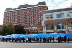 Étudiants marchant portant un long drapeau Images stock