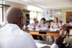 Étudiants masculins d'At Desk Teaching de tuteur de lycée dans le cours de Biologie photos libres de droits