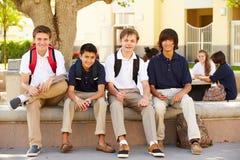 Étudiants masculins de lycée traînant sur le campus d'école Photo stock