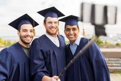 Étudiants masculins heureux prenant la photo par le bâton de selfie Photo stock
