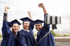 Étudiants masculins ou diplômés heureux prenant le selfie Image libre de droits