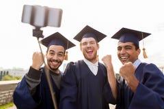 Étudiants masculins ou diplômés heureux prenant le selfie Photos stock