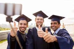 Étudiants masculins ou diplômés heureux prenant le selfie Photo stock