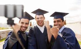 Étudiants masculins ou diplômés heureux prenant le selfie Image stock