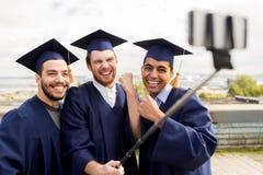 Étudiants masculins ou diplômés heureux prenant le selfie Images stock