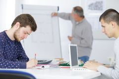 Étudiants masculins travaillant dans la salle de classe Images stock