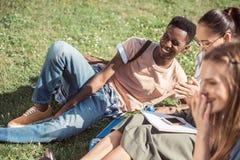 Étudiants multi-ethniques étudiant sur l'herbe Image stock