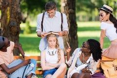 Étudiants multi-ethniques ayant l'amusement tout en étudiant ensemble sur le banc dans le parc Image stock