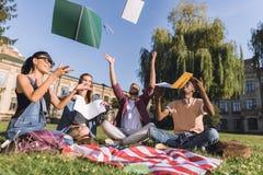 Étudiants multi-ethniques jetant des carnets Images stock