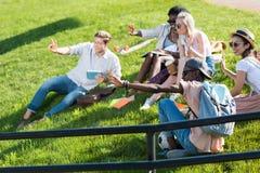 Étudiants multi-ethniques se reposant ensemble sur l'herbe verte en parc Photographie stock libre de droits