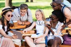 Étudiants multi-ethniques tenant des livres et des dispositifs numériques tout en agissant l'un sur l'autre en parc Photographie stock libre de droits